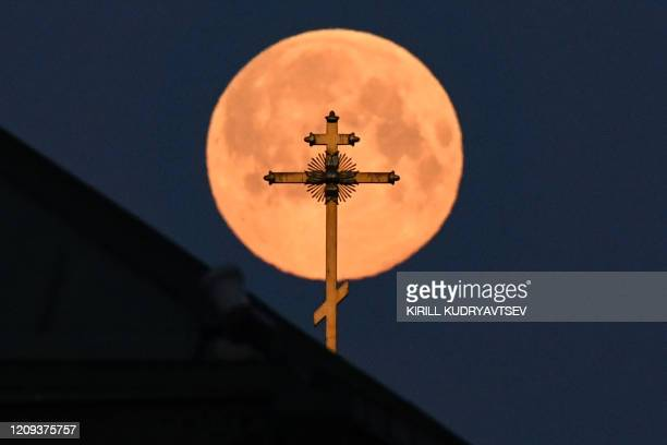 This picture taken early on April 8 2020 shows the closest supermoon to the Earth also known as a pink moon behind the cross on a church in downtown...