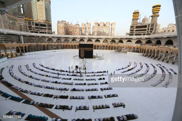 This picture taken early on May 24 2020 shows worshippers gathering before the Kaaba at the Grand Mosque in Saudi Arabia's holy city of Mecca to...