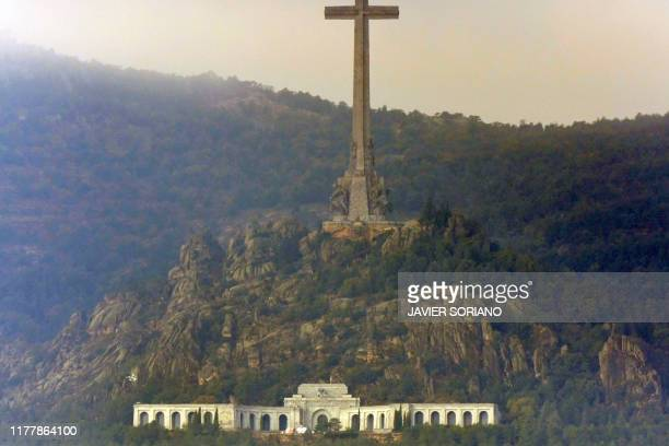 This picture taken from Collado Villalba shows an helicopter landing in the Valle de los Caidos mausoleum in San Lorenzo del Escorial on October 24...