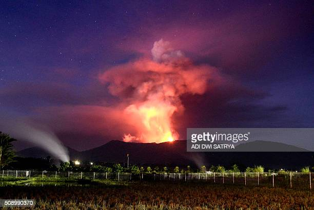 TOPSHOT This picture taken from Kawangkoan in Minahasa North Sulawesi on February 7 2016 shows Mount Soputan spewing hot lava as the mountain erupts...