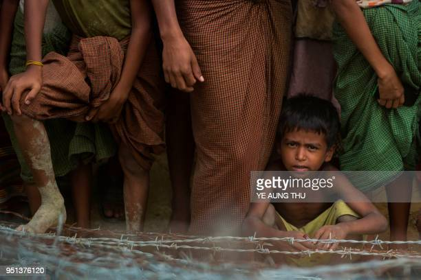 This picture taken from Maungdaw district Myanmar's Rakhine state on April 25 2018 shows Rohingya refugees gathering behind a barbedwire fence in a...