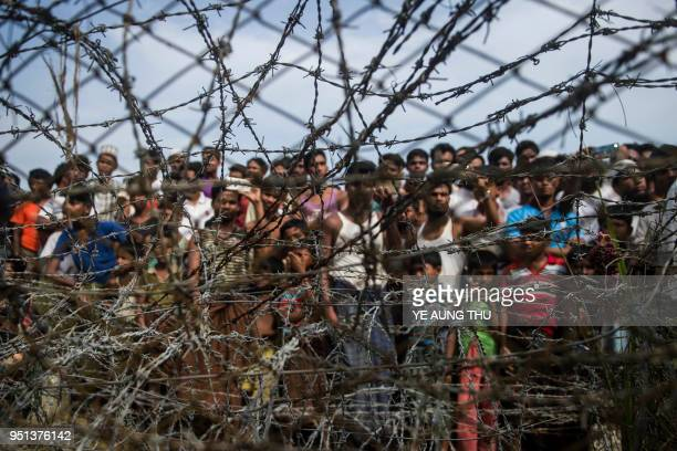 TOPSHOT This picture taken from Maungdaw district Myanmar's Rakhine state on April 25 2018 shows Rohingya refugees gathering behind a barbedwire...