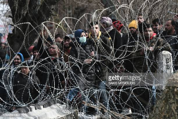 This picture taken from the Greek side of the Greece-Turkey border near Kastanies, shows migrants waiting on the Turkish side on March 2, 2020. -...