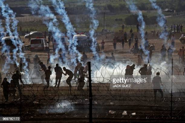 TOPSHOT This picture taken from the southern Israeli kibbutz of Nahal Oz across the border with the Gaza Strip shows Palestinian protesters taking...