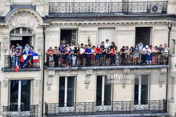 TOPSHOT This picture taken from the terrace of the Publicis drugstore in Paris on July 15 2018 shows people celebrating from a balcony after France...