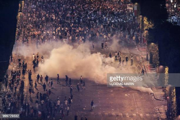This picture taken from the top of the Arch of Triumph on July 15 2018 shows police throwing teargas at people rioting after celebrations of the...
