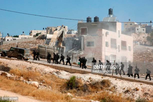 This picture taken from the West Bank on July 22 2019 shows Israeli security forces tearing down one of the Palestinian buildings still under...