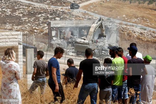 This picture taken from the West Bank on July 22 2019 shows Palestinians looking at Israeli security forces tearing down one of the Palestinian...