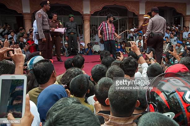 This picture taken in Banda Aceh on September 19 2014 shows a hooded officer caning an Aceh man for gambling in Banda Aceh Gay sex could be...