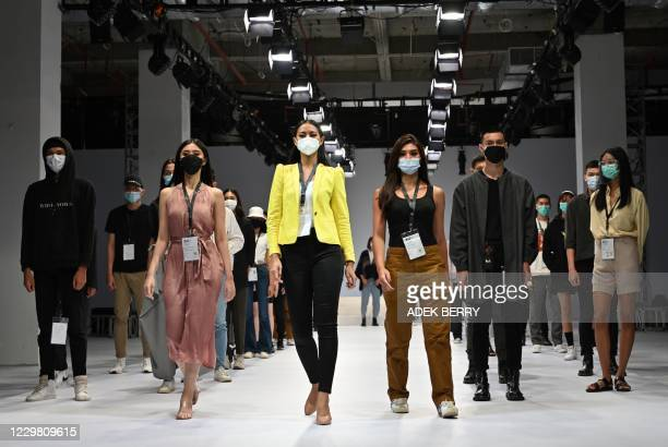 This picture taken in Jakarta on November 6, 2020 shows models wearing face masks during a rehearsal for the opening of Jakarta Fashion Week that was...