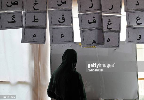This picture taken in Kabul on October 12, 2011 shows Afghan woman Furista at a literacy class in a shelter run by women for Afghan women. In the...