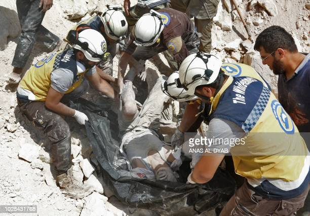 TOPSHOT This picture taken in Kafr Ain on September 7 shows members of the Syrian Civil Defence also known as the White Helmets carrying a victim...