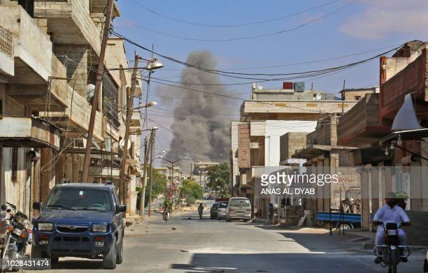 TOPSHOT This picture taken in Kafr Ain on September 7 shows smoke rising as government forces target the city 4 kilometers east of Khan Shaykhun in...