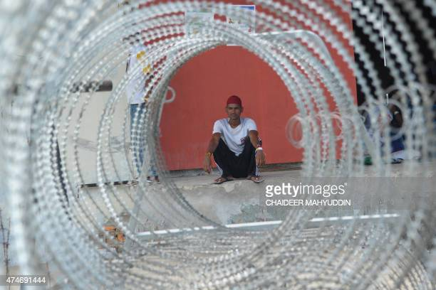 This picture taken in Langsa on May 24 2015 shows a Bangladeshi migrant sitting at a shelter Indonesia has begun search and rescue operations for...