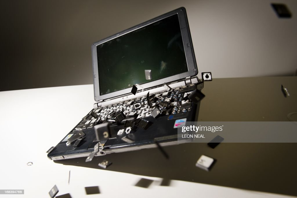 This picture taken in London on May 9, 2013 is a posed image of a laptop computer's keyboard shattering into pieces after an impact. AFP PHOTO/Leon Neal / AFP / LEON
