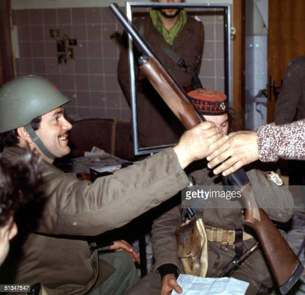 This picture taken in November 1991 in the Croatian town of Vukovar shows Yugoslav army captain Miroslav Radic being given a gun by a Serbian...