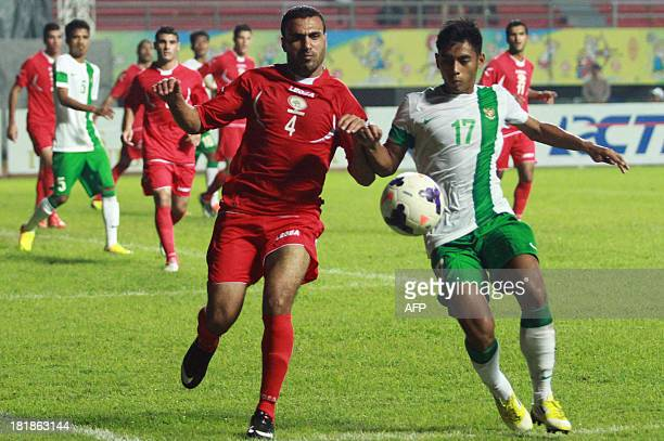 This picture taken in Palembang on September 24 2013 shows Palestinian player Haled AK Mahdi challenging Syahroni of Indonesia during a football...