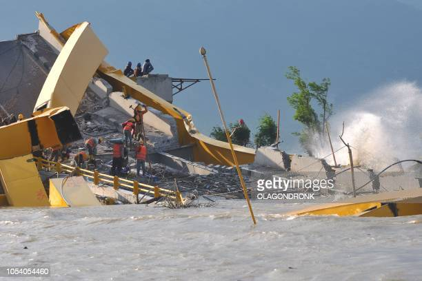 This picture taken in Palu on October 26 2018 shows Indonesian workers working on a damaged bridge hit by quaketsunami in Palu Indonesia's deadly...