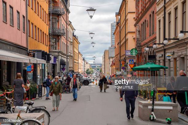 This picture taken in Stockholm, Sweden, on August 31 shows people walking in a street in Stockholm, amid the novel coronavirus pandemic. - While...