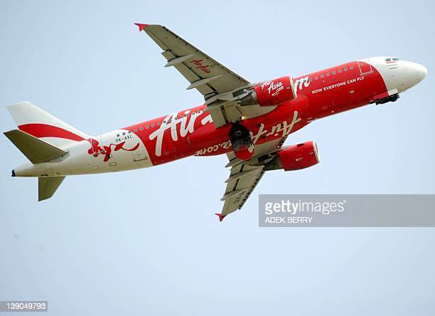This picture taken in Tangerang on February 15 2012 shows an AirAsia airplane is flying over the SukarnoHatta airport in Tangerang AirAsia is...