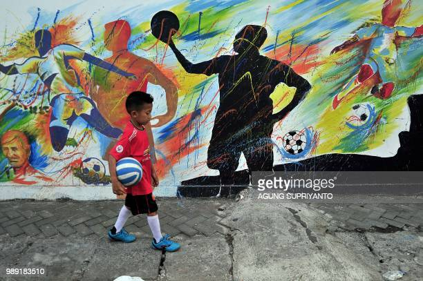 This picture taken in Tegalrejo Yogyakarta on July 1 2018 shows a young boy walking past a FIFA World Cup 2018 theme
