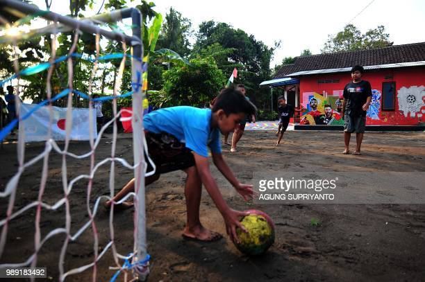 This picture taken in Tegalrejo Yogyakarta on July 1 2018 shows young boys playing football near a FIFA World Cup 2018 theme