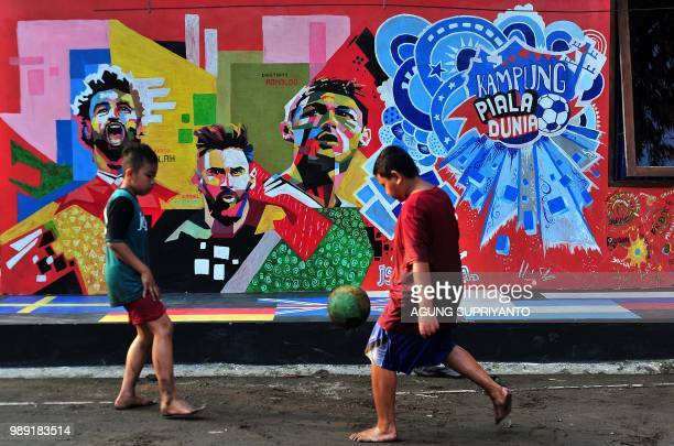 TOPSHOT This picture taken in Tegalrejo Yogyakarta on July 1 2018 shows young boys playing football next to a mural featuring the FIFA World Cup 2018...