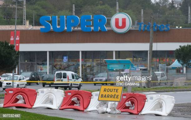 This picture taken in the town of Trebes southwestern France on March 24 2018 shows a sign reading 'Closed road' at the entrance of the Super U...