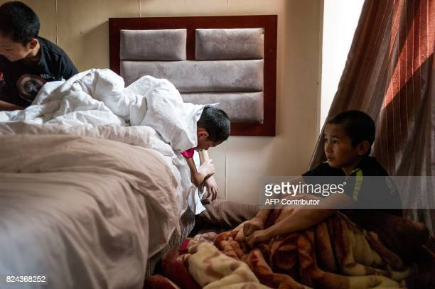 This picture taken June 2 2017 shows Abieamu and Jihushuojie resting in their hotel room before fighting at an underground fight club in Chengdu...