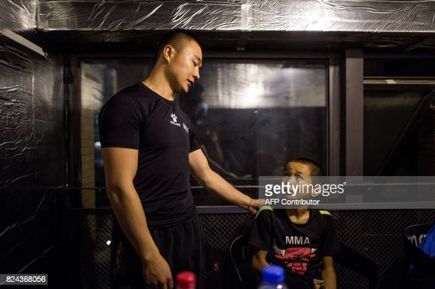 This picture taken June 2 2017 shows Abieamu listening to his coach before fighting at an underground fight club in Chengdu Abieamu is among the kids...