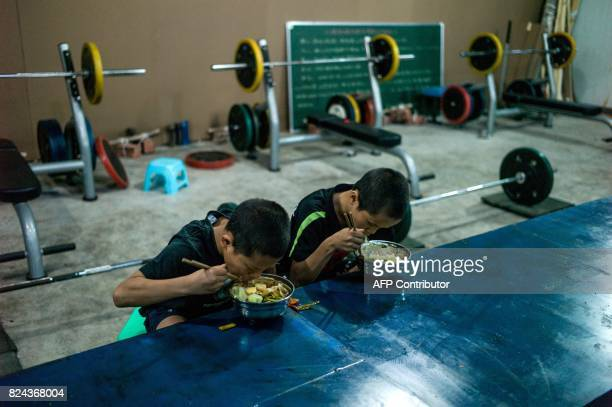 This picture taken June 2 2017 shows Jihushuojie and Abieamu eating dinner before taking part in mixed martial arts fighting in Chengdu Abieamu and...