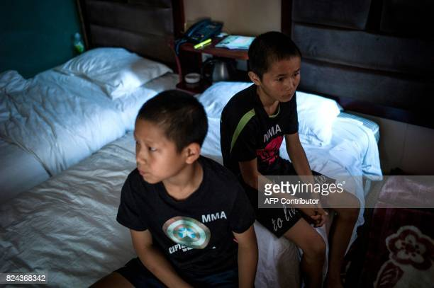 This picture taken June 2 2017 shows Jihushuojie and Abieamu waiting in their hotel room before taking part in mixed martial arts fighting at an...
