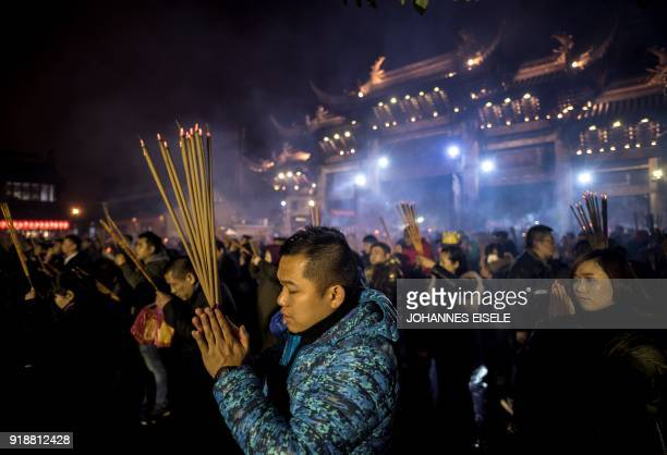 This picture taken late on February 15 2018 shows people praying with incense sticks to celebrate the Lunar New Year marking the Year of the Dog at...