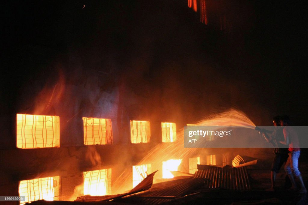 This picture taken on 24 November, 2012 shows Bangladeshi people and firefighters trying to extinguish a fire in a garment factory in Savar, 30 kilometres north of Dhaka. The death toll from a fire at a Bangladeshi factory soared to at least 121 as rescue workers recovered 112 bodies on November 25, the national fire chief told AFP.