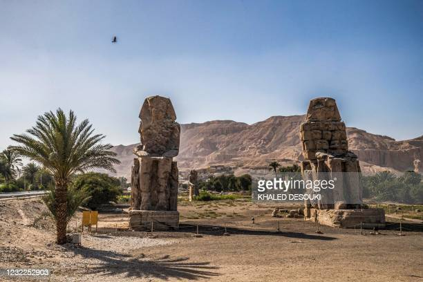 This picture taken on April 10, 2021 shows a view of the Colossi of Memnon, two massive stone statues of the 18th dynasty Egyptian pharaoh Amenhotep...