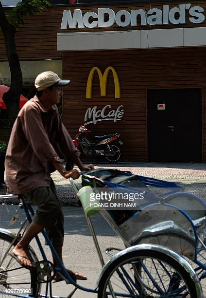 This picture taken on April 11 2015 shows a 'cyclo' driver passing a newly opened outlet of the US fastfood giant MacDonald's in downtown Ho Chi Minh...