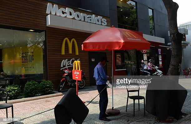 This picture taken on April 11 2015 shows a guard standing outside a newly opened outlet of the US fastfood giant MacDonald's in downtown Ho Chi Minh...