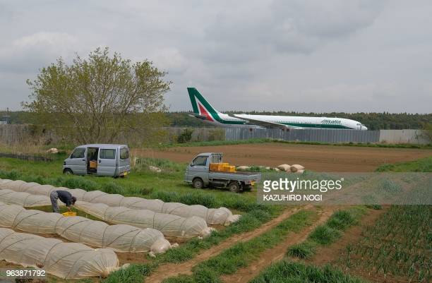 This picture taken on April 12 2018 shows a farmer working in a farm beside a runway of Narita airport Tokyo's main international gateway in Chiba...