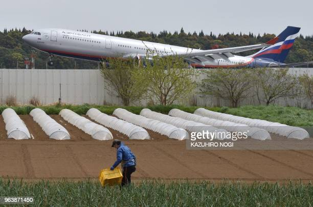 This picture taken on April 12 2018 shows a farmer working on a vegetable field beside a runway of Narita airport Tokyo's main international gateway...