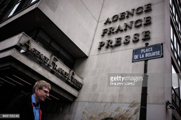 This picture taken on April 12 2018 shows a pedestrian walking past the headquarters of the French news agency Agence FrancePresse in Paris Board...