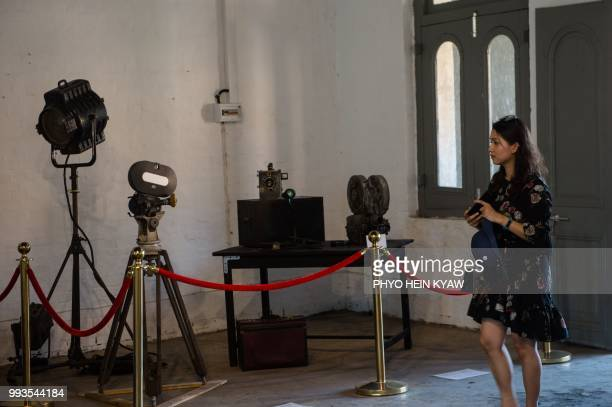 This picture taken on April 12 2018 shows a visitor views a display of vintage camera and projector at the Myanmar film heritage exhibition at the...