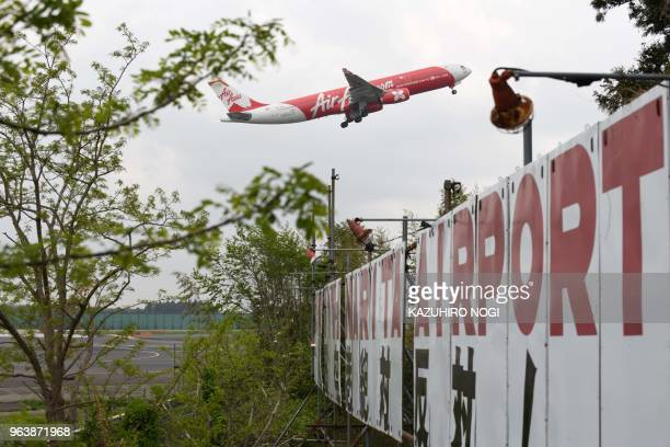 This picture taken on April 12 2018 shows an airplane taking off over a protest board against runway construction at a farmland encircled by Narita...