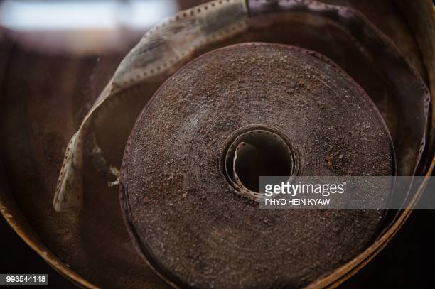 This picture taken on April 12 2018 shows damaged film reel displayed during the Myanmar film heritage exhibition at the historic Secretariat...