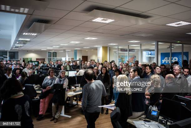 This picture taken on April 12 2018 shows employees of Agence FrancePresse during a meeting at the offices of the French news agency in Paris Board...