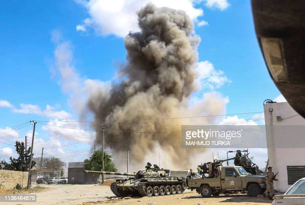 This picture taken on April 12 2019 shows a smoke plume rising from an air strike behind a tank and technicals belonging to forces loyal to Libya's...