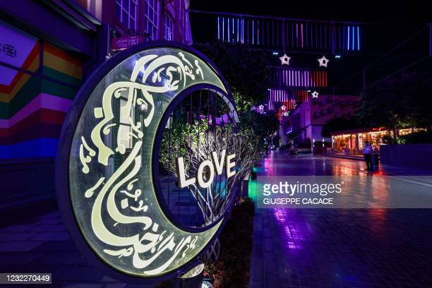 This picture taken on April 12, 2021 shows a view a large lit decoration in the shape of a crescent moon bearing calligraphic text in Arabic reading...