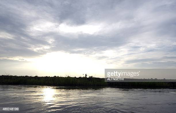 This picture taken on April 13 2014 shows a Mundari fisherman walking along the river Nile on April 13 2014 near Terekeka Conflict in South Sudan has...