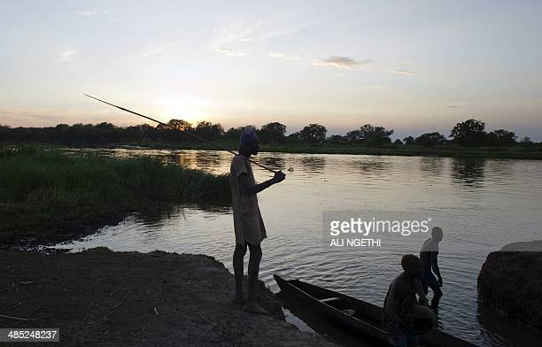 This picture taken on April 13 2014 shows Mundari youth fishing with a spear along the Nile on April 13 2014 near Terekeka Conflict in South Sudan...