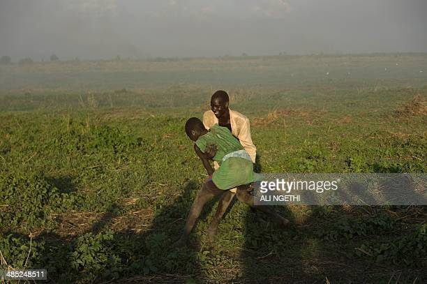 This picture taken on April 13 2014 shows Mundari youth wrestling along the Nile on April 13 2014 near Terekeka Conflict in South Sudan has triggered...