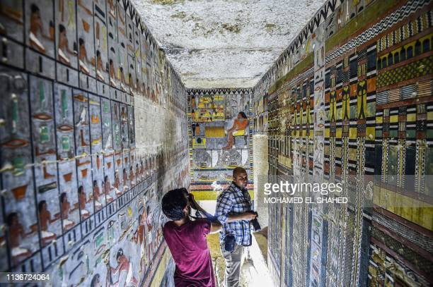 TOPSHOT This picture taken on April 13 2019 shows journalists filming inside the newlydicovered tomb of the ancient Egyptian nobleman Khewi dating...